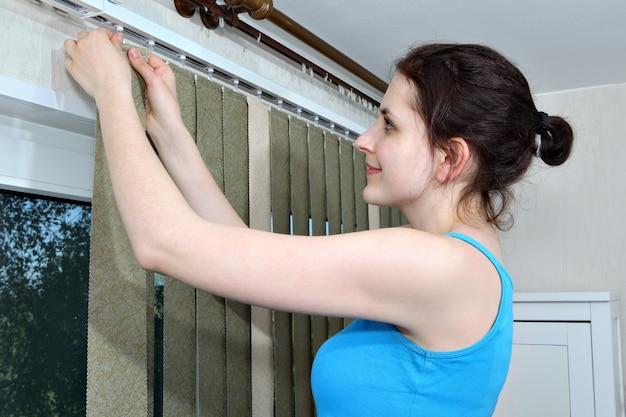 Meisje opknoping jaloezieën verticale blinde stof latten haak op rail.