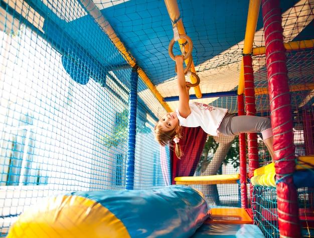 Meisje opknoping op kleurrijke speeltuin