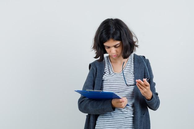 Meisje opstijgen bril, kijkt uit over notities op klembord in t-shirt