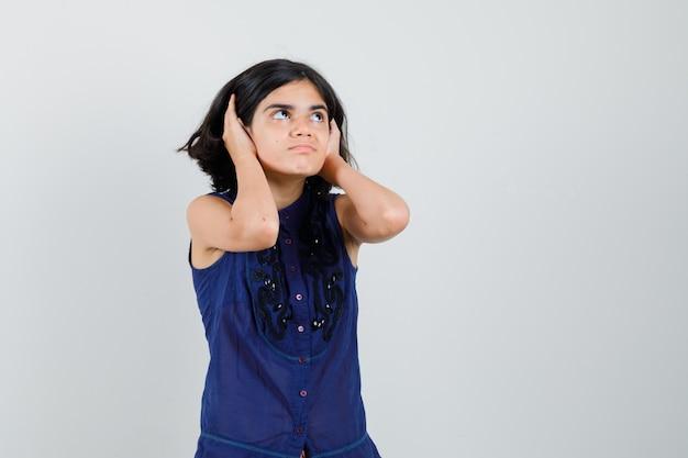 Meisje opzoeken terwijl hand in hand op oren in blauwe blouse.