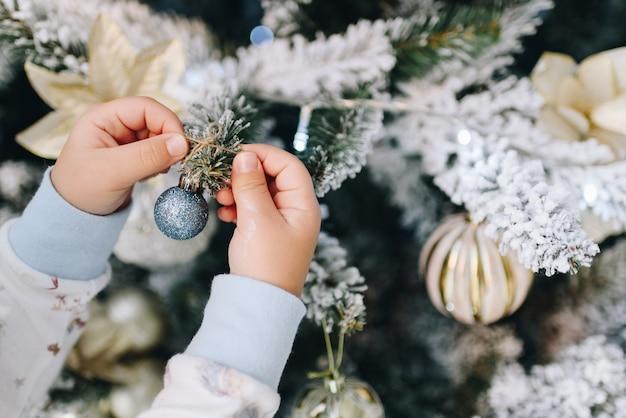 Meisje ornamenten op kerstboom te zetten