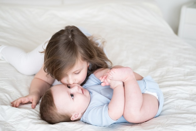 Meisje oudere zus kuste haar kleine broertje van de babyjongen op bed thuis.