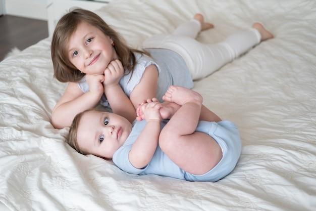 Meisje oudere zus liggend op bed met haar kleine broertje van de babyjongen thuis