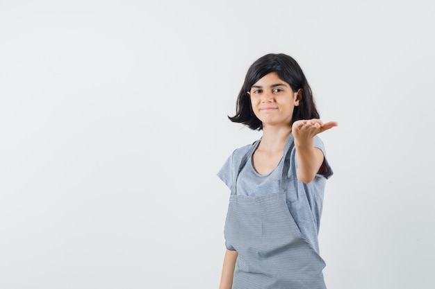 Meisje outstretching hand in t-shirt en kijkt zacht, vooraanzicht.