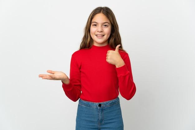 Meisje over geïsoleerde witte die copyspace denkbeeldig op de palm houdt om een advertentie en met omhoog duimen in te voegen