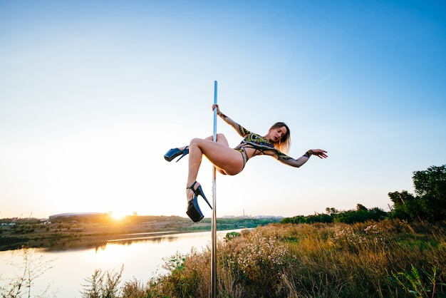 Meisje paaldanseres voert een element op de paal met de split
