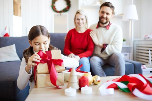 Meisje pakt het kerstcadeau uit terwijl haar ouders haar vrolijk aankijken.