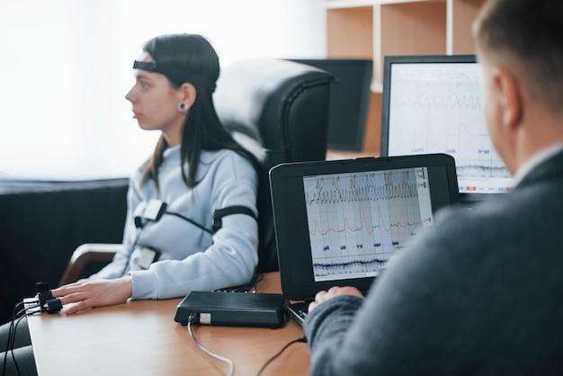 Meisje passeert leugendetector in het kantoor. vragen stellen. polygraaftest