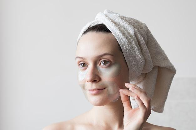 Meisje past hydrogelpleisters op haar gezicht toe, ochtendroutine. hoge kwaliteit foto