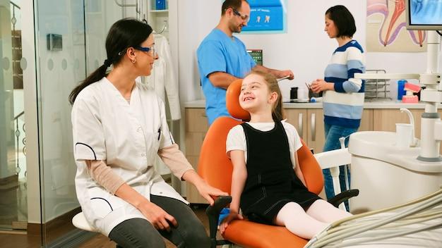 Meisje patiënt wachten pediatrische stomatologist vrouw zitten in tandartsstoel terwijl man assistent praten met moeder op achtergrond. tandarts die met meisje bespreekt alvorens mondelinge gezondheid te onderzoeken.