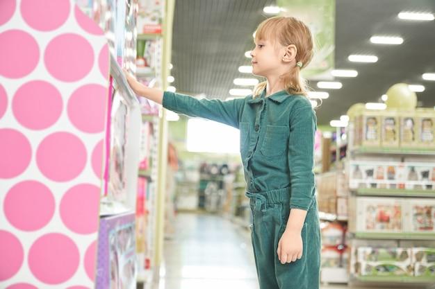 Meisje permanent in de buurt van planken met speelgoed, kijken, kiezen.