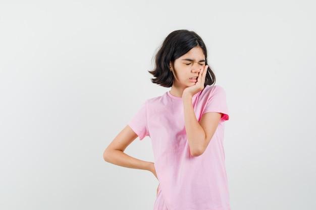 Meisje permanent in denken pose in roze t-shirt en op zoek vergeetachtig, vooraanzicht.