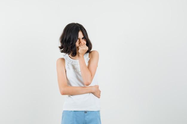 Meisje permanent in denken pose in witte blouse, korte broek en op zoek somber, vooraanzicht.