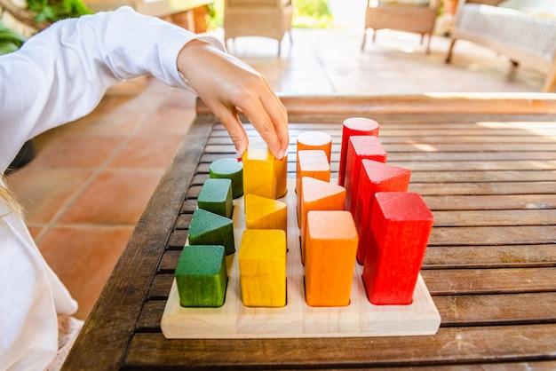 Meisje plaatsen van de blokken die een geometrische montessori puzzel van kleuren