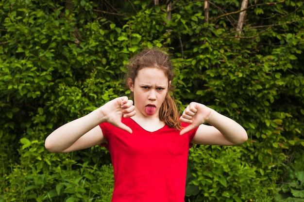 Meisje plagen met tong uitsteekt camera kijken in park