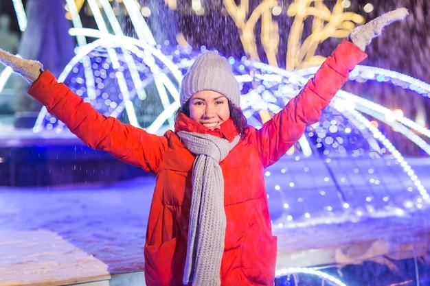 Meisje plezier op kerstversiering lichten straat. jonge gelukkig lachende vrouw met stijlvolle gebreide sjaal en jas buitenshuis. model lachen. winter wonderland stadsbeeld, nieuwjaarsfeest.