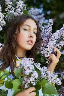 Meisje poseert in een lila struik in het voorjaar. romantisch portret van een kind in bloemen in het zonlicht