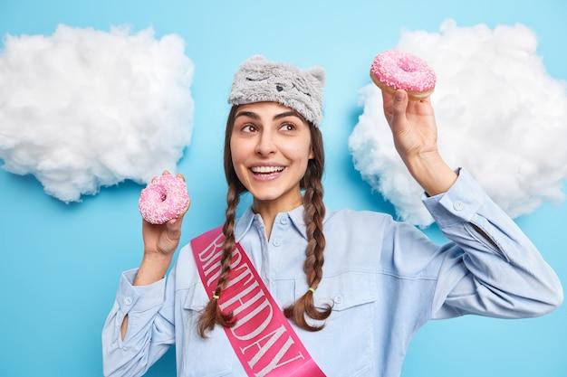 Meisje poseert met twee donuts in handen lacht tandjes geconcentreerd boven voelt zich erg gelukkig heeft plezier op haar verjaardag poseert tegen blauw