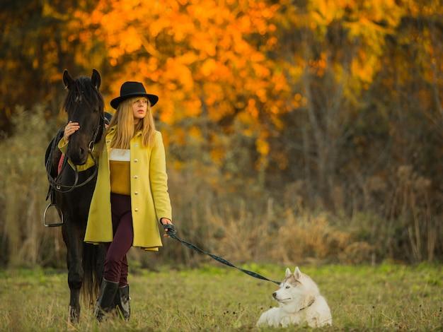Meisje poseren met een paard en een hond