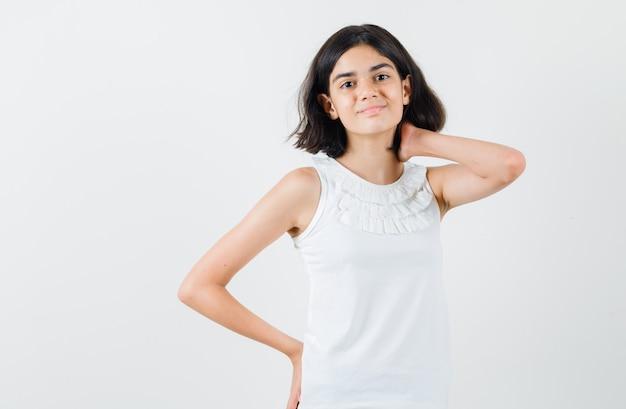 Meisje poseren met hand op nek in witte blouse en op zoek vrolijk, vooraanzicht.