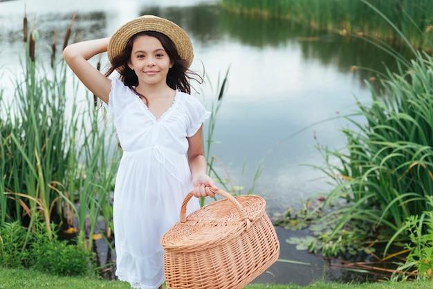 Meisje poseren met picknickmand aan het meer