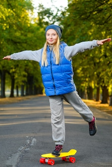 Meisje poseren met skateboard buitenshuis