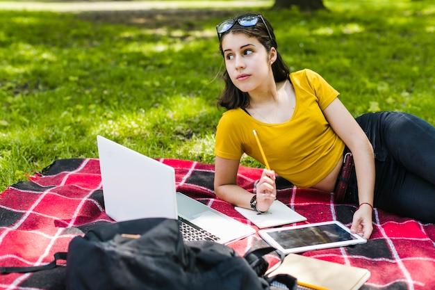 Meisje poseren met technologie, potlood en notitieboekje