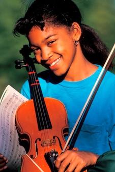 Meisje poseren met viool en bladmuziek