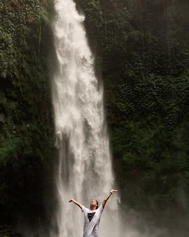 Meisje poseren tegen de achtergrond van een waterval