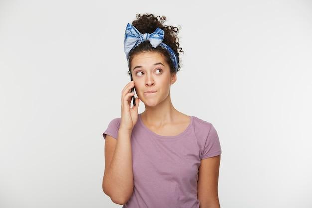Meisje praat aan de telefoon en kijkt naar de zijkant
