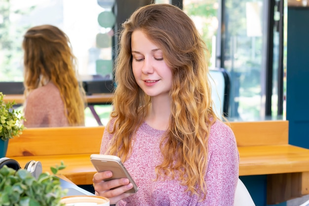 Meisje praat over de telefoon. meisje schrijft een bericht aan de telefoon.