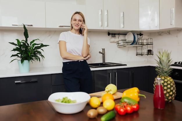 Meisje praat over een telefoon en glimlacht tijdens het koken van de lunch in de keuken thuis
