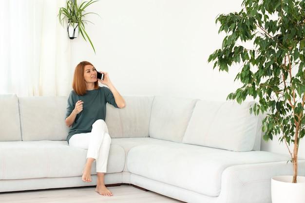 Meisje praten aan de telefoon. glimlachende echte vrouw thuis. wit interieur, kopie ruimte