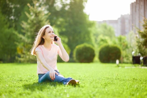 Meisje praten aan de telefoon zittend in het park op het gras