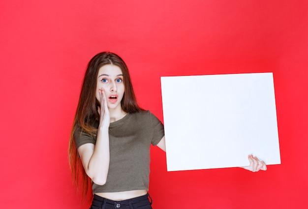 Meisje presenteert een vierkant infobord en ziet er verrast en verward uit.