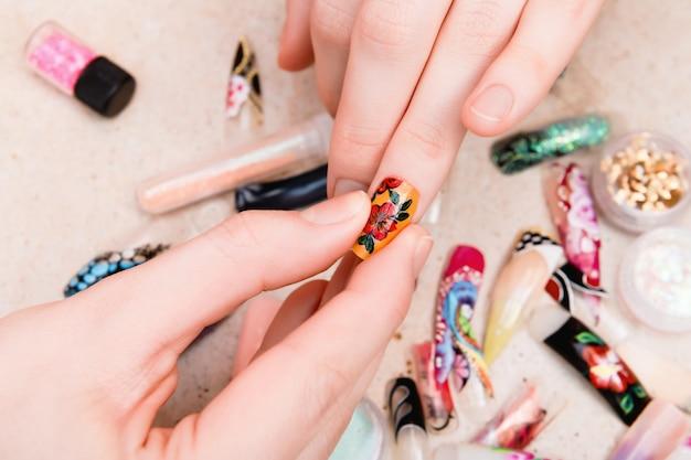 Meisje probeert kunstmatige nagels tips met bloem nagel ontwerp