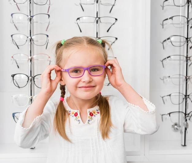 Meisje probeert op een bril bij de optische winkel