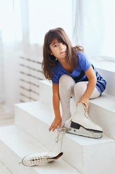 Meisje probeert op een grote schaatsen. klein kind en schaatsen