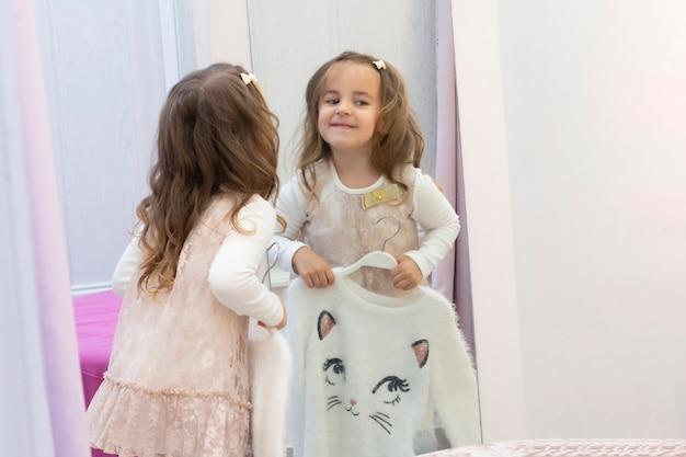 Meisje probeert op kleding in een paskamer in een kledingwinkel.