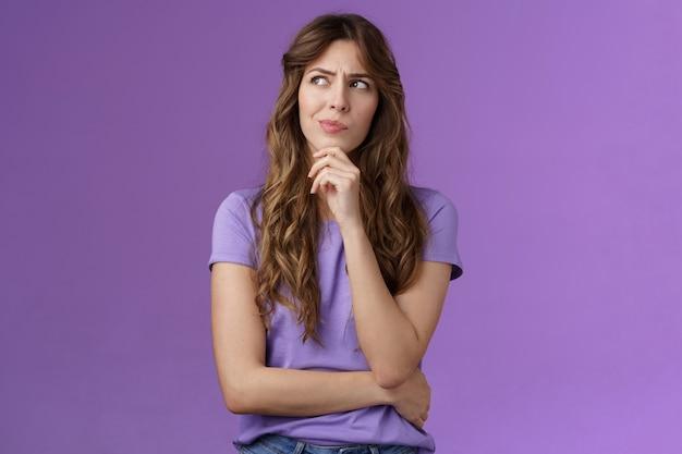 Meisje probeert op te lossen probleem denken oplossing maken hmm gezicht grijns fronsen nadenkend wegkijken aanraken kin nadenken maken van keuze beslissen hoe handelen wat staan paarse achtergrond gericht