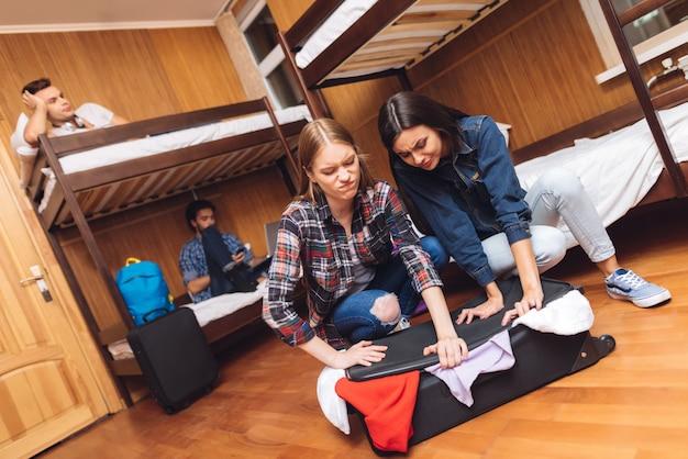 Meisje probeert vriendin dicht valise te helpen.