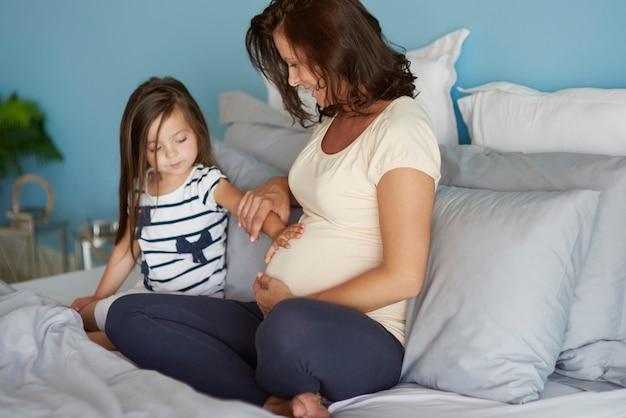 Meisje raakt de buik van haar moeder aan