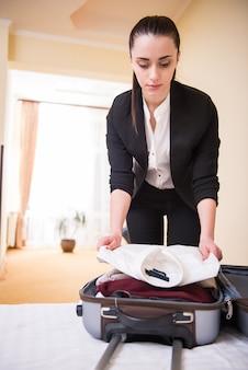 Meisje reed de kamer in en pakte haar koffer uit.