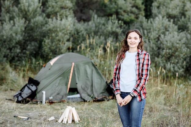 Meisje reiziger op de achtergrond van een tent in de natuur