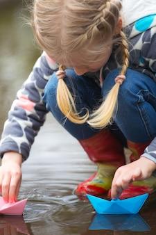 Meisje rent de roze papieren boot in een plas in de regen, lente