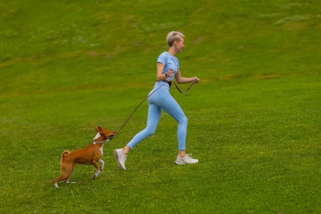 Meisje rent met een hond in het park op het gazon bij zonsondergang, loopt een huisdier in de natuur.