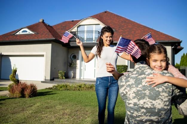 Meisje rent naar haar militaire vader voor het huis terwijl vrouw zwaait met amerikaanse vlaggen