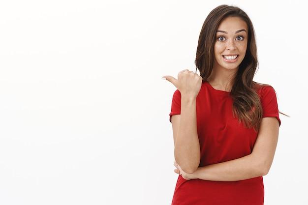 Meisje roddelend over vreemd ding dat ze achter zag, opgewonden en enthousiast staan in rood t-shirt, duim wijzend naar lege witte kopieruimte, geïntrigeerd grijnzend, staande studiomuur