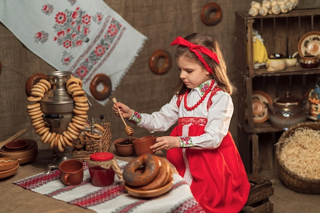 Meisje rode hoofdband dragen en sieroverhemdzitting bij lijsthoogtepunt van voedsel en grote samovar die maslenitsa vieren