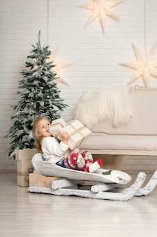 Meisje rodelen met kerst geschenkdozen